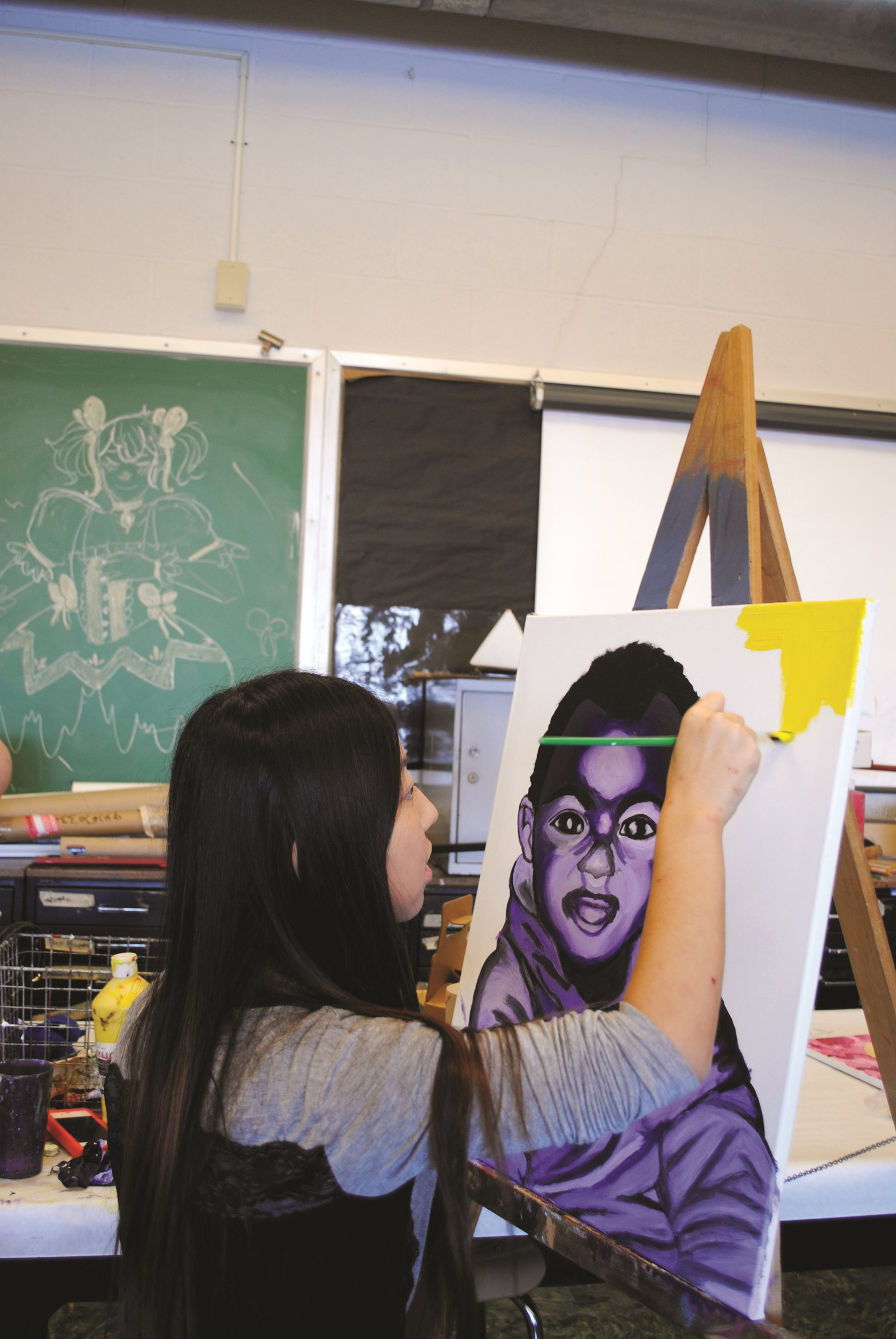Photo of student painting a canvas